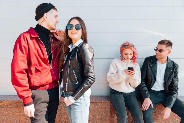 Jeune couple, debout, tandis que, autre, paire, regarder, dans, smartphone