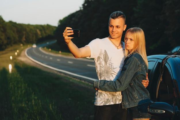 Jeune couple debout à la voiture garée sur le bord de la route de l'autoroute et prenant selfie