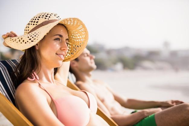 Jeune couple, délassant, fauteuil, plage