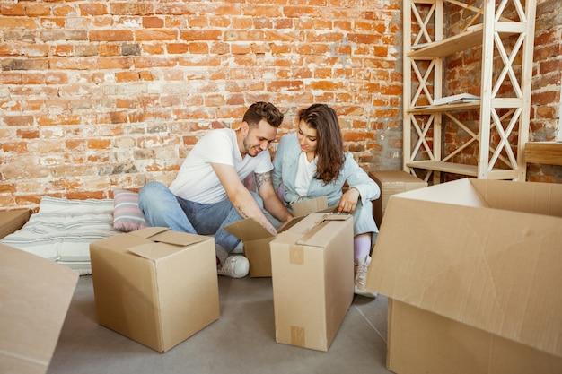 Jeune couple a déménagé dans une nouvelle maison ou un nouvel appartement. déballer les cartons ensemble, s'amuser le jour du déménagement. ayez l'air heureux, rêveur et confiant. famille, déménagement, relations, premier concept de maison.