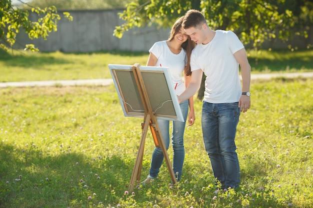 Jeune couple dessin au chevalet par des peintures panachées colorées. jolie jeune femme et beau mec s'amuser avec des peintures à l'extérieur.