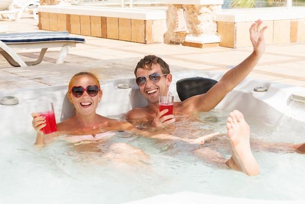 Jeune couple de détente dans la piscine jacuzzi