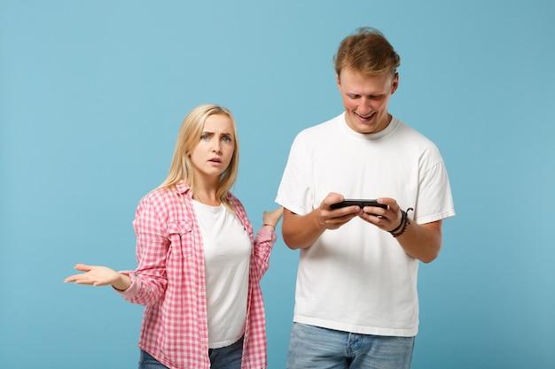 Jeune couple deux amis homme et femme en t-shirts vides roses blancs posant