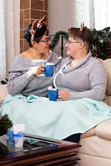 Un jeune couple de deux femmes assises sur un canapé buvant du chocolat chaud à noël