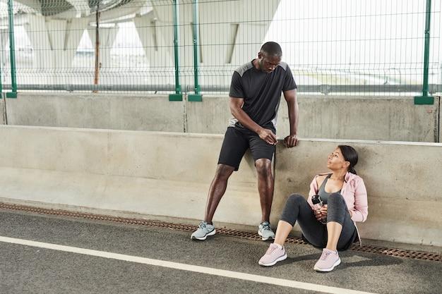 Jeune couple discutant d'exercices entre eux pendant leur entraînement sur le stade