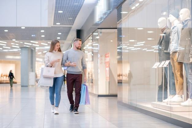 Jeune couple discutant de la nouvelle collection en vitrine en passant par l'un des départements du centre commercial pendant la vente saisonnière