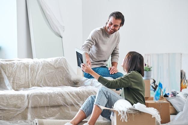 Jeune couple discutant de la photo dans le cadre tout en riant l'homme pointant sur elle et expliquant à sa femme ce qui est si drôle à ce sujet