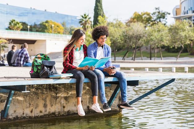 Jeune couple diversifié apprennent ensemble assis dehors dans le parc