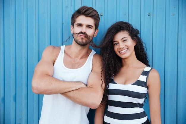 Jeune couple drôle faisant la moustache avec les cheveux et s'amusant sur le mur bleu