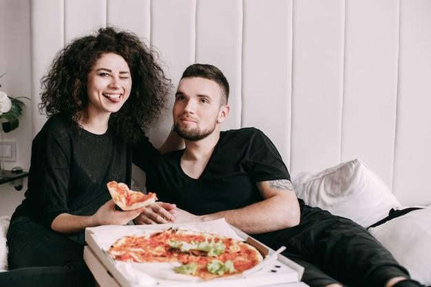 Un jeune couple drôle mange une pizza couchée sur le lit