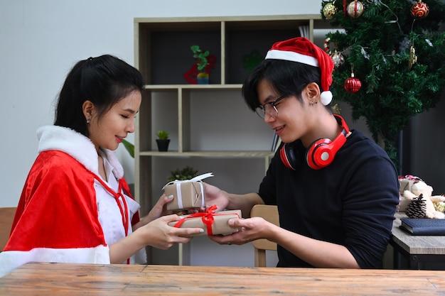 Jeune couple échangeant des cadeaux de noël tout en célébrant noël ensemble.
