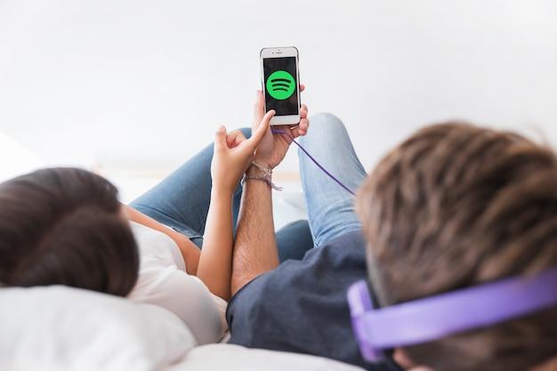 Jeune couple écoutant de la musique avec l'application spotify