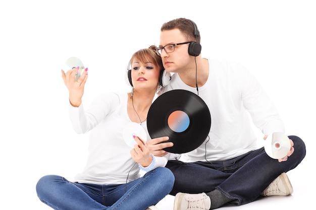 Jeune couple écoutant de la musique sur fond blanc