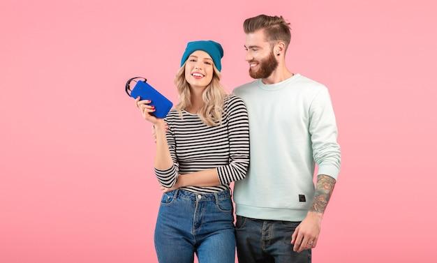 Jeune couple écoutant de la musique sur haut-parleur sans fil portant une tenue élégante et cool souriant posant sur rose
