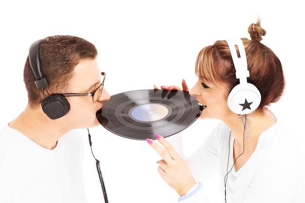 Un jeune couple écoutant de la musique et jouant avec du vinyle sur fond blanc