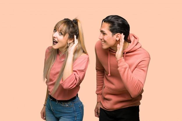 Jeune couple, écoute, quelque chose, mettre, main, oreille