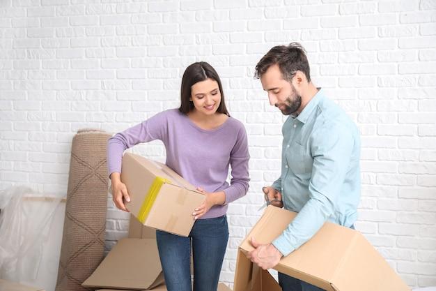 Jeune couple avec des effets personnels après avoir emménagé dans une nouvelle maison