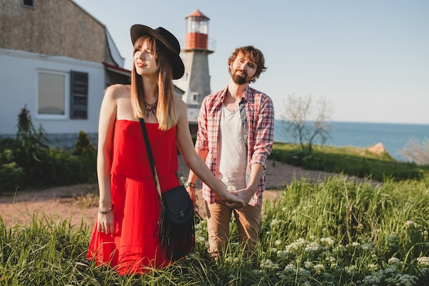 Jeune couple élégant amoureux dans la campagne, style bohème hipster indie, vacances de week-end, tenue d'été, robe rouge, herbe verte, main dans la main, souriant