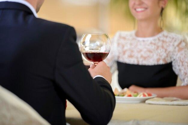 Jeune couple élégant, boire du vin assis dans un restaurant