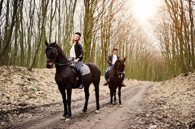 Jeune couple élégant à cheval sur la forêt d'automne