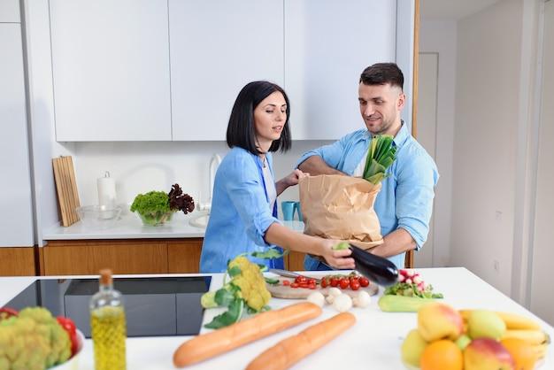 Jeune couple élégant déballant ensemble des produits frais du marché dans une cuisine confortable.