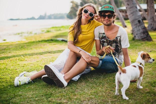 Jeune couple élégant hipster amoureux assis sur l'herbe jouant avec un chien sur la plage tropicale