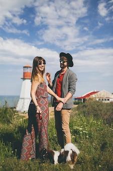 Jeune couple élégant hipster amoureux marchant avec un chien dans la campagne