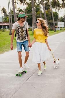 Jeune couple élégant hipster amoureux en vacances avec chien et planche à roulettes, s'amuser