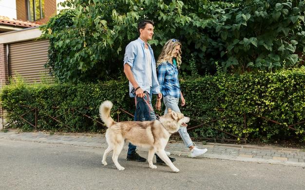 Jeune couple élégant marchant avec un chien dans la rue. homme et femme heureux avec race husky