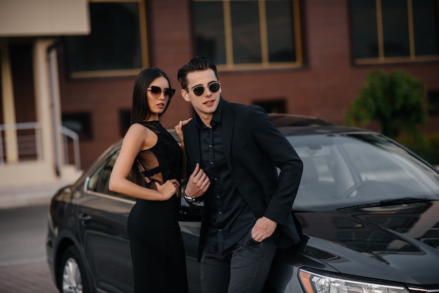 Un jeune couple élégant en noir se tient près de la voiture au coucher du soleil. mode et style