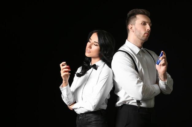 Jeune couple élégant avec parfum sur fond sombre