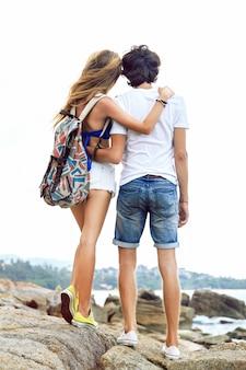 Jeune couple élégant posant sur la plage, voyage avec sac à dos, vêtu de vêtements d'été élégants et de baskets.