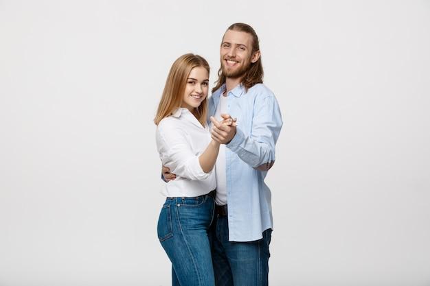 Jeune couple élégant en tissu casual dansant sur isolé sur fond de studio blanc.
