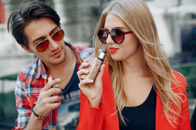 Jeune couple élégant avec vape dans une ville