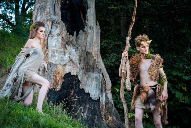 Jeune couple d'elfes amoureux implantation sur une branche dans une forêt magique en plein air sur la nature
