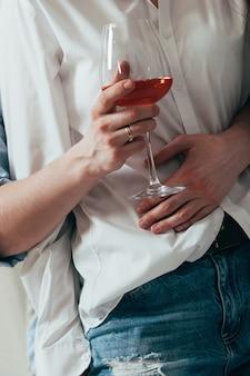 Un jeune couple embrassant et buvant du vin