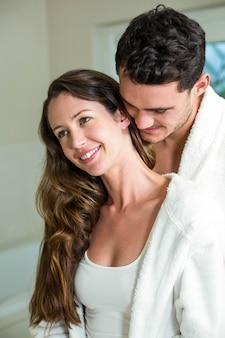 Jeune couple embrassant dans la salle de bain et souriant