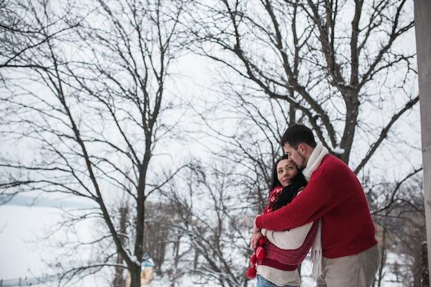 Jeune couple embrassant en forêt d'hiver