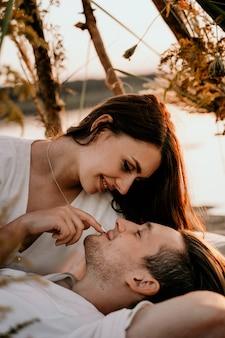 Jeune couple embrassant et s'embrassant sur la côte du coucher du soleil. histoire d'amour romantique. jeune fille brune dans une robe légère.