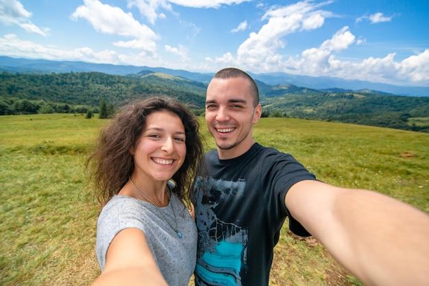 Jeune couple embrasse et prend selfie avec un paysage de montagne incroyable.