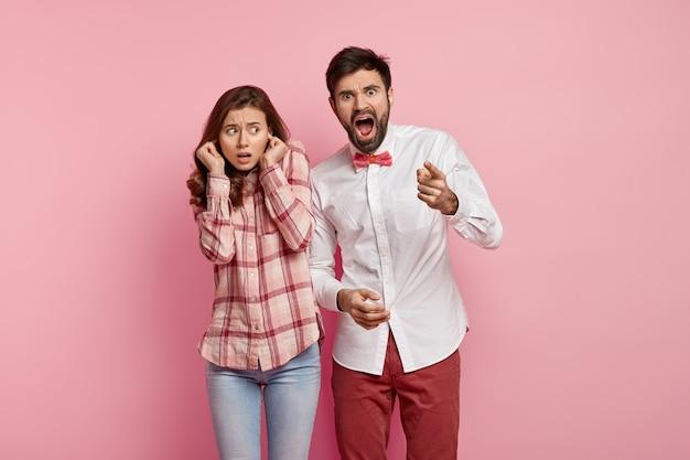 Jeune couple émerveillé. un homme barbu effrayé crie de panique, pointe son doigt vers la caméra