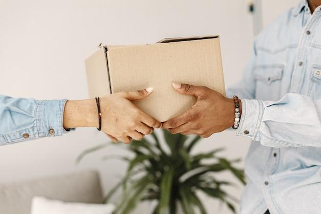 Jeune couple emménageant dans une nouvelle maison ensemble. couple afro-américain avec des boîtes en carton.