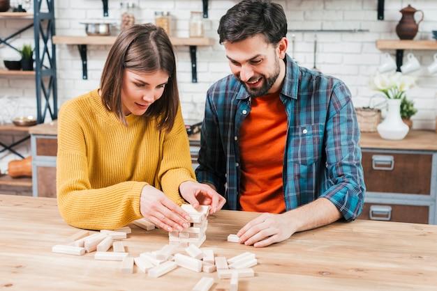 Jeune couple empiler le bloc de bois sur la table dans la cuisine