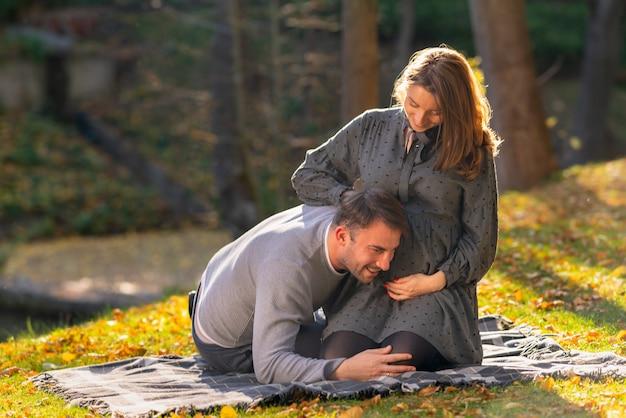 Jeune couple enceinte partageant un moment tendre alors que le mari écoute les battements de cœur de son enfant à naître pendant qu'ils se détendent sur un tapis dans le parc