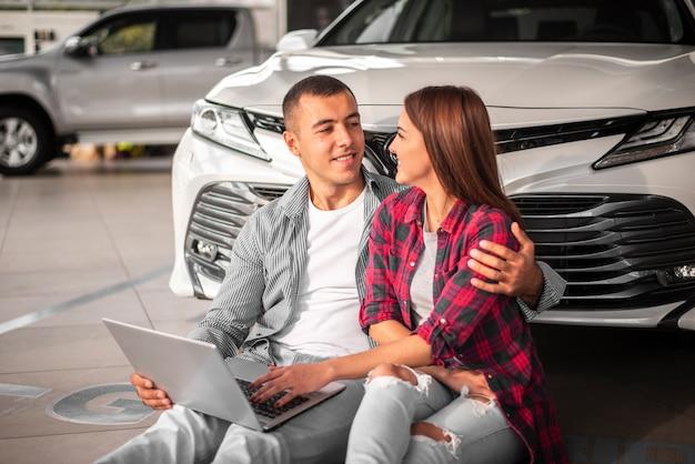 Jeune couple ensemble chez un concessionnaire automobile