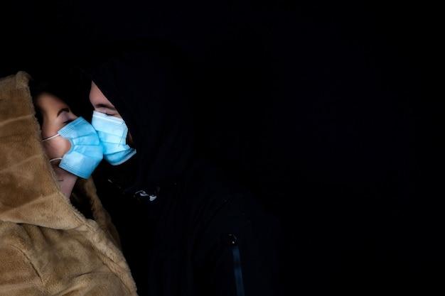 Jeune couple ensemble dans l'obscurité avec veste d'hiver avec masques médicaux de protection