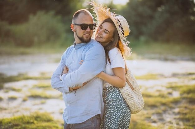 Jeune couple, ensemble, dans parc, coucher soleil