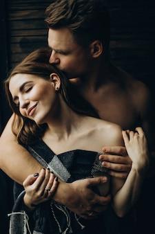 Jeune couple ensemble sous la couverture à la maison