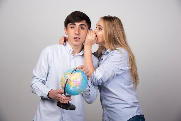 Jeune couple enthousiaste planifiant ses vacances tenant un globe et chuchotant.