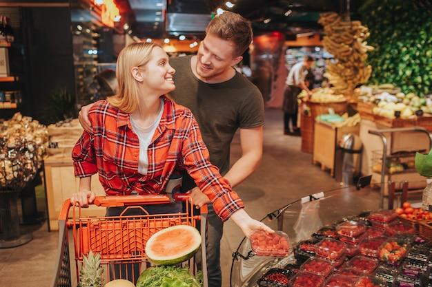 Jeune couple en épicerie poussant le graphique